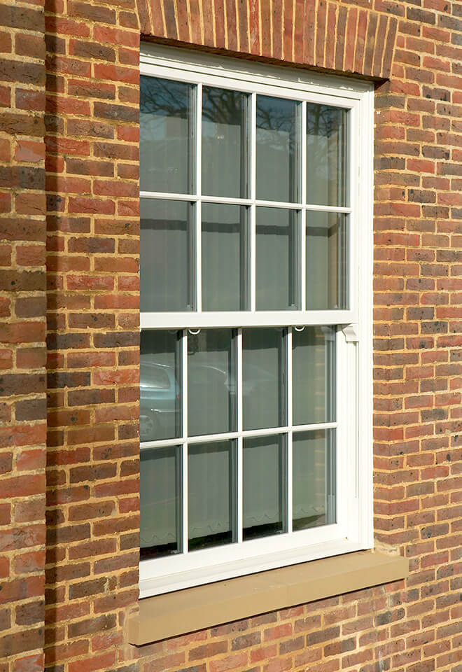 White uPVC sliding sash windows with astragal bars